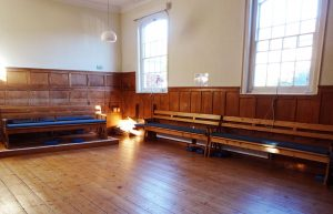 A large room with wooden floors, wooden panelling and benches.